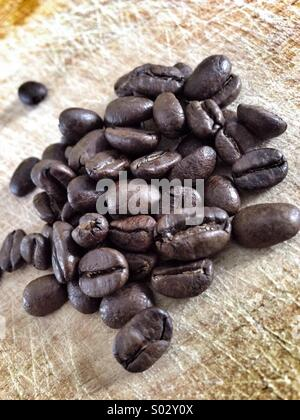 Coffee beans on cutting board - Stock Image