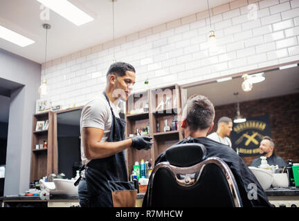 A mature man client talking to haidresser and hairstylist in barber shop. - Stock Image