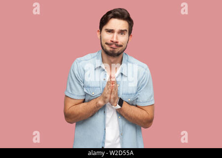 Please help me, or forgive. Portrait of sad hopeful handsome bearded young man in blue casual style shirt standing, looking at camera and begging. ind - Stock Image