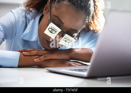 Young Woman Covering Her Eyes With Adhesive Notes On Desk In Office - Stock Image
