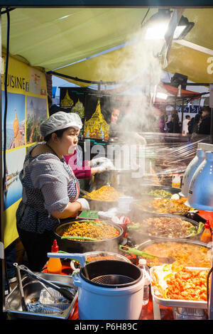 Asian food selling various traditional steaming hot and freshly cooked spicy dishes in Street market, Hackney, London, England. - Stock Image