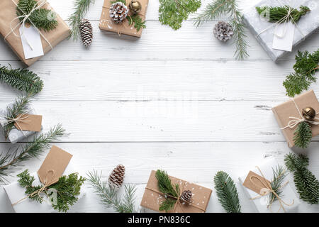 Christmas gift, knitted blanket and fir branches on wooden white background. Flat lay,top view. - Stock Image