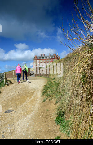Dog walkers wearing brightly coloured jackets walking along the coastal path near the Headland Hotel in Newquay in Cornwall. - Stock Image