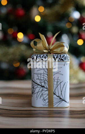 Cute and stylish Christmas present. The gift is on a wooden surface and there is a beautiful, colorful Christmas three with a lot decorations. - Stock Image