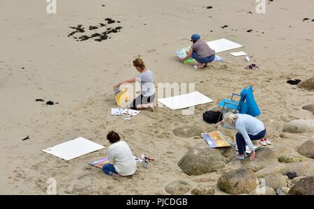 People painting pictures of a beach scene,Sennen Cove,Cornwall,England,UK - Stock Image