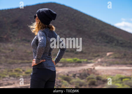 Curly woman viewed from rearoking the way and stand in the outdoor natural place- hiking equipment and sport active lifestyle for active people - trek - Stock Image