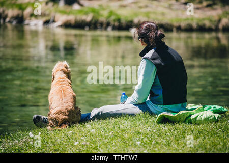 Lone woman and her dog friend resting in Lago Ghedina, an alpine lake in Cortina D'Ampezzo, Dolomites, Italy - Stock Image