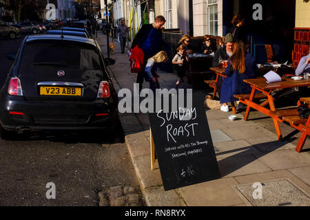 A sign advertises a Sunday Roast outside a Public House (Pub) in Primrose Hill in London - Stock Image