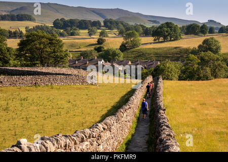 UK, Yorkshire, Wharfedale, Grassington, Sedber Lane, people walking down lane leading to Linton Falls in summer - Stock Image