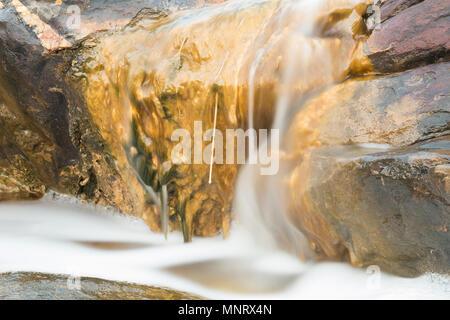 Water flows over algae-covered sandstone rocks in Penneshaw on Kangaroo Island, South Australia, Australia. - Stock Image