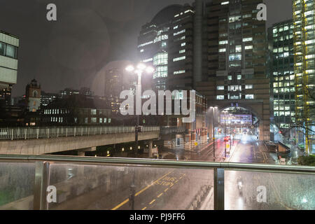 View of rain falling over city at night - Stock Image
