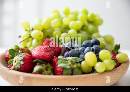 Wooden bowl with fruits: strawberries, blueberries and green grapes. - Stock Image