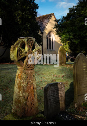 Portrait English village church and cemetery with tombstones in early morning sunlight - Stock Image