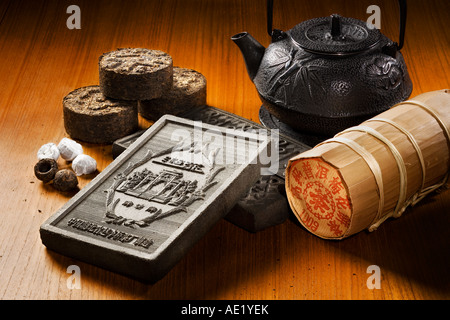 A tea kettle, tea bricks and tea rolls wrapped in fancy packaging placed on a table top. - Stock Image