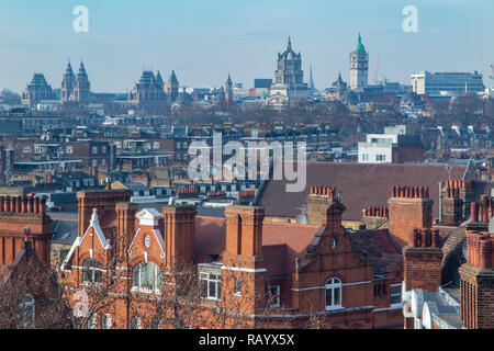 The London skyline, Chelsea chimneys and roof tops in the foreground and the historic Natural History museums in the distance - Stock Image