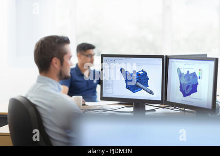 Engineers designing gearboxes using computer aided design (CAD) software in gearbox factory - Stock Image