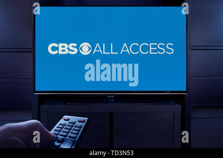A man points a TV remote at the television which displays the logo for the CBS All Access on demand video streaming service (Editorial use only). - Stock Image