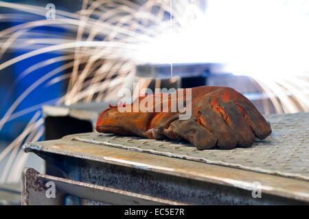 working glove in front of a flame of a welding torch - Stock Image