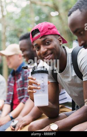 Portrait smiling man drinking water, preparing for hike - Stock Image
