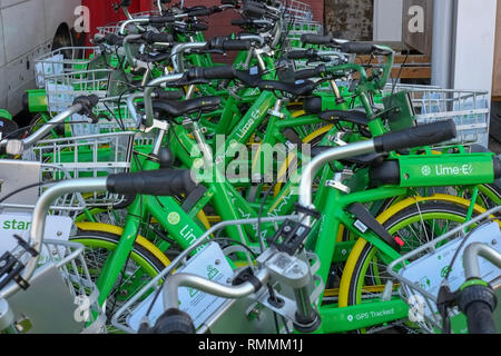 A cluster of Lime-E electric bikes are parked at a warehouse in West London - Stock Image