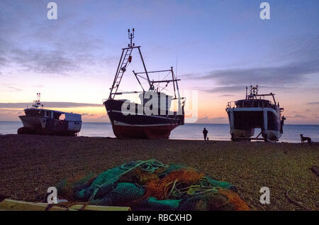 Hastings, East Sussex, UK. 9th Jan 2019. Cold start to the day for dog walkers at dawn on the Stade Fishermen's Beach. Hastings has the largest beach launched fishing fleets in Europe. - Stock Image