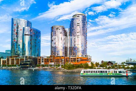 Ritz Carlton Hotel and The Towers at Elizabeth Quay with a TransPerth ferry going past - Stock Image