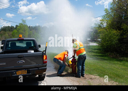 Village workers opening fire hydrant to flush out the water lines in Speculator, NY USA - Stock Image