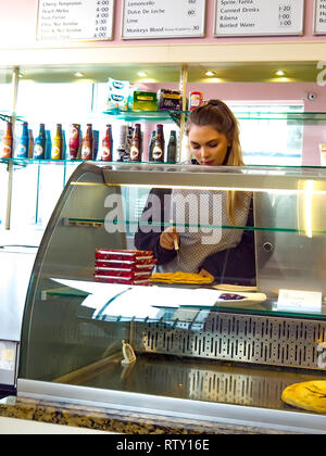 A young waitress in an ice cream parlour in North Yorkshire England carefully cutting a slice of home-made apple pie - Stock Image