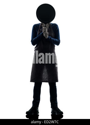 one  woman cooking hiding behind frying pan in silhouette studio isolated on white background - Stock Image