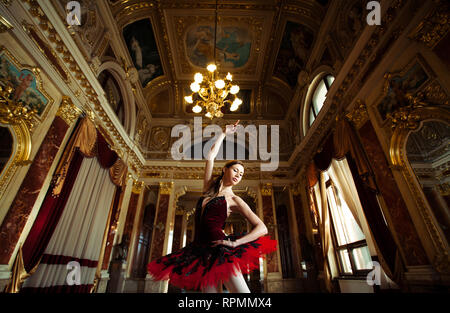Beautiful ballerina dancing in a hall with a chandelier in a red dress against the luxurious interior. - Stock Image