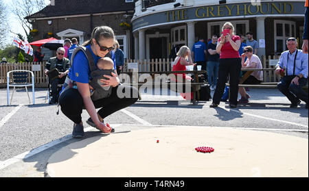 Crawley Sussex, UK. 19th Apr, 2019. Natalie Hollingshead with her 4 month old daughter Emily competing in the World Marbles Championship held at The Greyhound pub at Tinsley Green near Crawley in Sussex . The annual event has been held on Good Friday every year since the 1930s and is open to players from around the world Credit: Simon Dack/Alamy Live News - Stock Image
