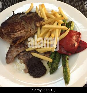 Tuna Steak, asparagus, red pepper and French fries. Meal for one - Stock Image