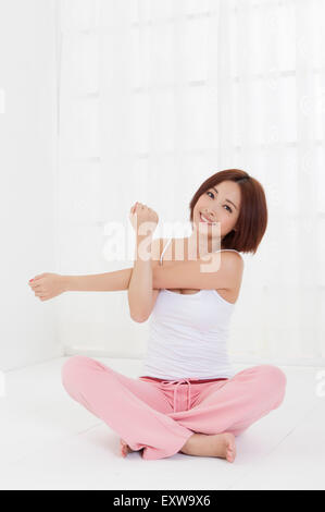Young woman sitting and smiling at the camera, - Stock Image