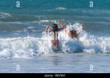 Two females having fun in the sea at Fistral in Newquay in Cornwall. - Stock Image
