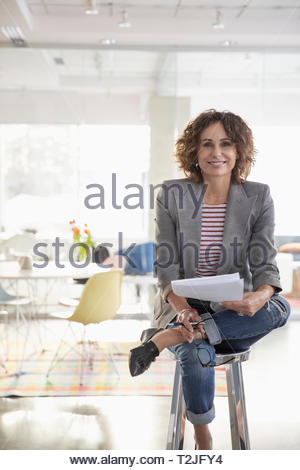 Portrait confident businesswoman in office - Stock Image