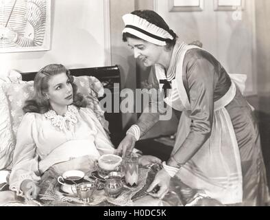 Maid serving breakfast to woman lying in bed - Stock Image