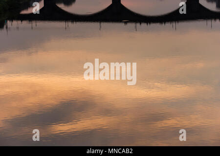 Beautiful reflection of clouds and sky in the arno river in florence italy of the ponte santa trinita taken from the ponte vecchio bridge at sunset - Stock Image