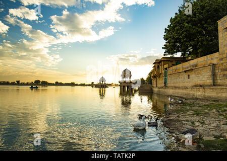 Spectacular view of the Gadi Sagar Lake (Gadisar) with ancient temples during sunset. - Stock Image