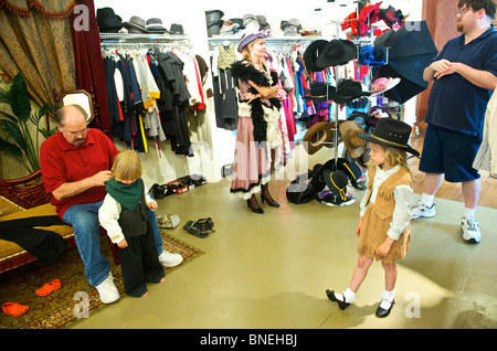 Tourist family getting ready in western style at Wildwest clothing for photo shoot in Galveston, USA - Stock Image