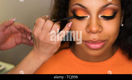 Makeup artist apply mascara on lashes african american girl. Evening make-up. Closeup portrait - Stock Image