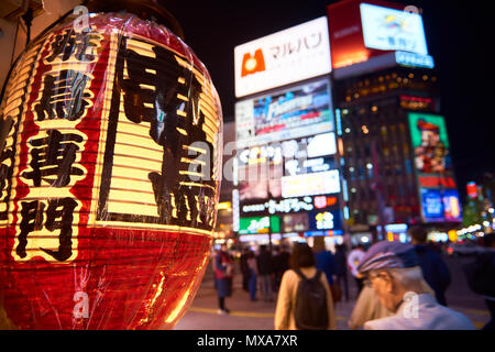 Yakitori Japanese lantern in focus in the foreground at night, with bright colourful outdoors in Susukino region of Sapporo, Hokkaido, Japan. - Stock Image