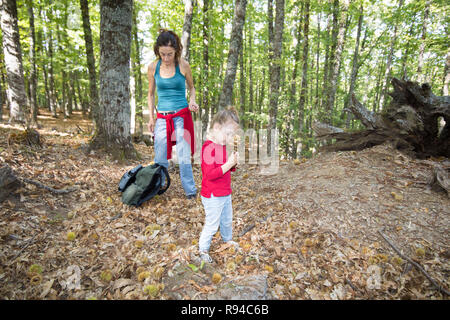 four years age blonde child with red shirt, blue jeans and pigtail, with a chestnut in hand, near mother woman with backpack, in autumn forest - Stock Image