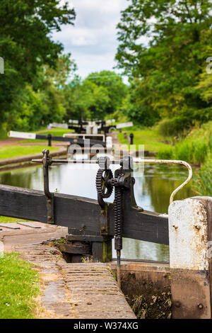 Detail of a lock paddle mechanism with a flight of locks in the background on the Tardebigge Locks, Worcester and Birmingham Canal, Worcestershire - Stock Image