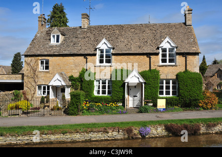 Houses beside the River Eye, Lower Slaughter, Gloucestershire - Stock Image