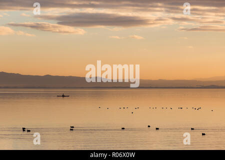 Beautiful view of a lake at sunset, with orange tones, birds on water and a man on a canoe - Stock Image