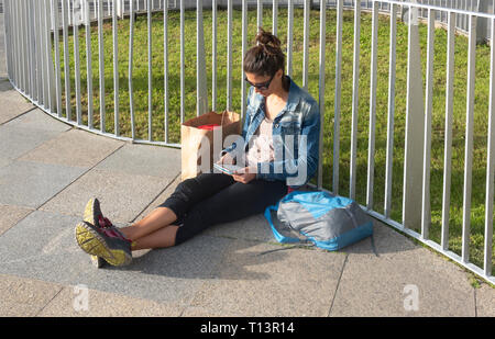 A young woman reading on a digital tablet and taking the sun in Seville - Stock Image