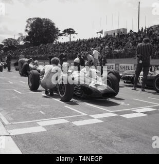 1960s, historical, motor racing at Crystal Palace race circuit in South London, London, England, UK. Drivers in their cars lined up on the track in the start grid with their team principals and mechanics beside them. - Stock Image