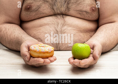 Obese  man holds in hands an apple and a doughnut concept of a tough choice between opposite alternatives (healthy food vs sweet food) - Stock Image