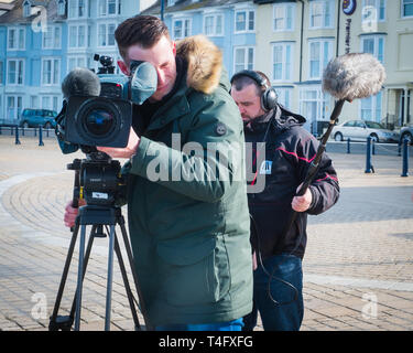 Media workers in the UK: A professional television crew  on location recording an item for broadcast, with the video camerman pointing his lens directly at the subject. UK - Stock Image