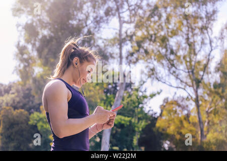 attractive blonde sports woman setting up phone app before workout outdoors at park, fitness accessories - Stock Image